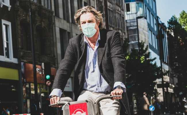 Ciclista usa máscara para evitar poluição