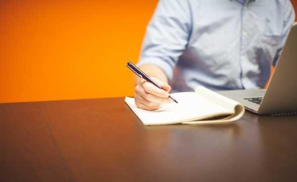 homem fazendo anotações em bloco de papel ao lado de laptop