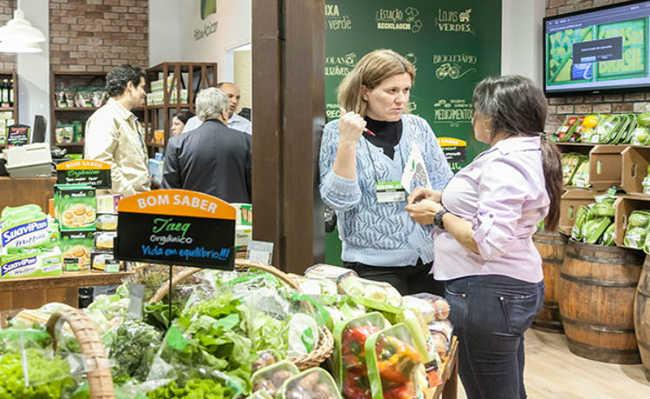 duas mulheres conversando ao lado de uma balcão com verduras orgânicas
