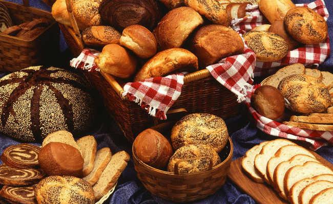 Pães de diversas variedades dispostos em um tecido azul, alguns em cestas, alguns no lençol.
