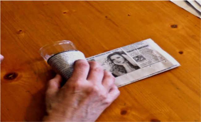 3. Enrole a tira de jornal em torno do copo, de forma que sobre um pedaço na parte inferior (ele comporá o fundo do vasinho). Coloque um pequeno pedaço de fita adesiva (a mesma será decomposta com o jornal) para fixar