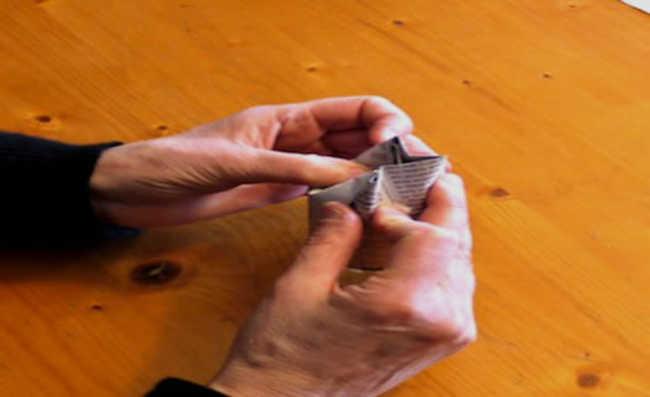 4. Para formar o fundo do vasinho, dobre a parte que sobrou e fixe-a com um pequeno pedaço de fita