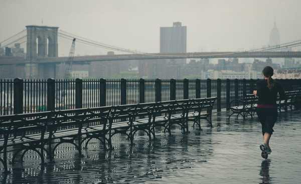garota correndo com a ponte do Brooklyng à distância