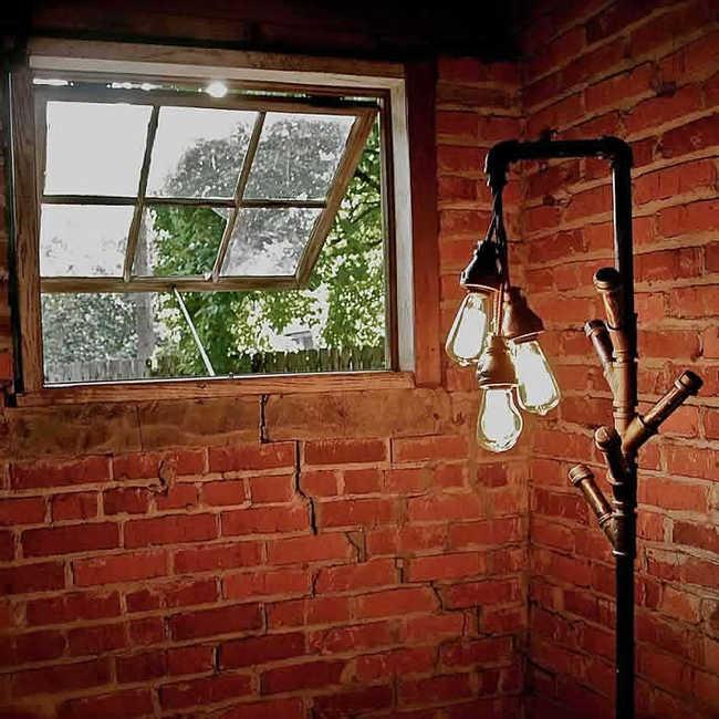 Duas paredes de tijolos vermelhos perpendiculares. A da esquerda que se encontra de frente a imagem possuí uma janela aberta que torna possível visualizar o sol brilhando por entre uma árvore verde cheia de folhas em um quintal. No canto direito da imagem uma luminária alta, quase do tamanho da janela, com três lâmpadas acesas penduradas no topo, como um chuveiro que cospe lâmpadas acesas. Durante a extensão da luminária a designer utilizou as conexões usadas em encanamentos para ter alguns pedaços de encanamento saindo de sua extensão como galhos nascendo em árvores