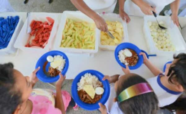Mulher servindo comida para crianças