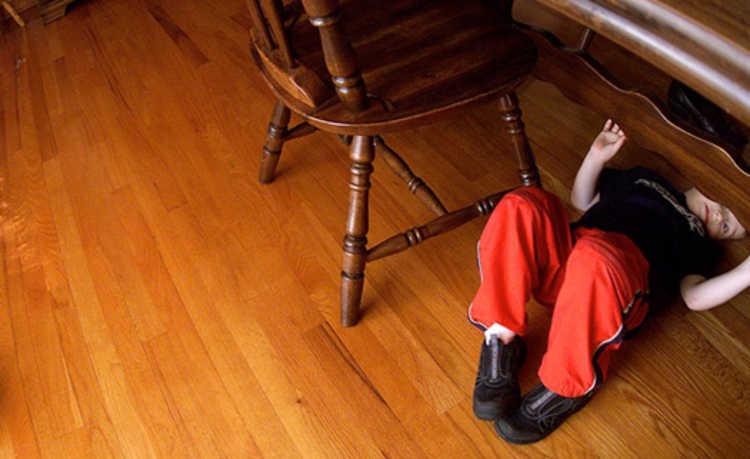 Menino deitado abaixo de uma mesa