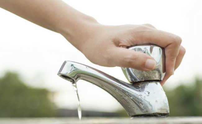 Mão fechando torneira
